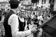Smile (Roberto Spagnoli) Tags: tocatì verona festival folk basque fotografiadistrada streetphotography flag biancoenero blackandwhite monocromo people fujix100t beauty girl smile glance look italy couple