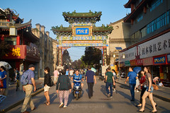 2018 Xi'an - Street Scenes 02 (C & R Driver-Burgess) Tags: scholarsstreet city walking pedestrians road footpath pavement arch entrance decorated gate historical xian 西安 man backpack goatee woman short denim shorts motorcycle scooter pedestrian strollling afternoon golden light