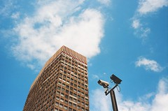 CCTV (flightofthealone) Tags: camera building architecture sky light blue colour london city plane saturated color cctv security dark black red modern minimal clouds morning leica m2 summicron 35mm film analogue street streetphotography