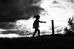 Innocence (markfly1) Tags: emsworth harbour barbed wire fence chained mesh rocks grass silhouettes high contrast white black post little girl walking kids children long bright light bush tree shade dark shadow mono monochromatic nikon d750 35mm manual focus lens big sky moody clouds grey storm stormy