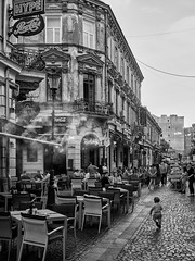 Aug 24, 2018 (pavelkhurlapov) Tags: child running street building cafe chair cobblestone oldtown monochrome streetphotography lamppost balcony sign adult pub architecture neon road people city