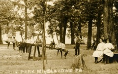 Seesawing at Hoffer Park, Middletown, Pennsylvania (Cropped) (Alan Mays) Tags: ephemera postcards realphotopostcards rppc photos photographs foundphotos hoffer hofferpark parks playgrounds seesaws seesawing teetertotters toys children boys girls men clothes clothing dresses trees treestumps stumps middletown pa dauphincounty pennsylvania antique old vintage baum jkbaum photographers playthings