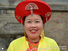 2018-03d Northeast Vietnam (89) (Matt Hahnewald) Tags: matthahnewaldphotography facingtheworld people character head face eyes catchlights mouth teeth expression lookingcamera smile story traditional taoist costume hat consent concept humanity living dedication commitment travel tourism culture tradition custom lifestyle socialevent religion taoism religious cultural festival folklore temple devotee bacha northern vietnam vietnamese southeastasian individual oneperson female mature woman photo physiognomy nikond3100 primelens nikkorafs50mmf18g 50mm 4x3 horizontal street portrait closeup headshot fullfaceview red color posingcamera smiling cheerful fullfigured lipstick fun earrings clarity yellow