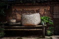 Courtyard in Lijiang (Rod Waddington) Tags: china chinese yunnan lijiang basket bench wooden wood grinding wheels plants mud brick lattice outdoor house