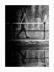 Out of Darkness (Dave Fieldhouse Photography) Tags: streetphotography street monochrome mono blackandwhite bnw reflections reflection person canal towpath bridge birmingham city citycentre urban shadows lightandshade water barrier handrail fujifilm fuji fujixt2 fujinon35mmf2 walk walker wwwdavefieldhousephotographycom