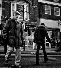 Gifts, Gadgets and cards. (Neil. Moralee) Tags: neilmoralee neilmoraleenikond7100 man people street candid hip town road walking old mature hat coat wellington somerset uk neil moralee nikon d7100 black bandw blackandwhite photography contrast photo portrait europe men woman monochrome monotone mono bw urban white life lpov low point view crossing