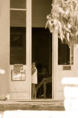 Curiosity (fillzees) Tags: candid street girl outdoor shop doorway portal window bw sign foliage shrubbery woman skirt seated greece crete greek ελλάσ ελλάδα ηράκλειο