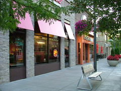 Shops at Prairiefire (jHc__johart) Tags: neon window flower reflection sign sidewalk hangingplanter kansas prairiefirecomplex bench awning pole