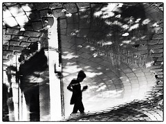 pushkin's square in reflection (Pomo photos) Tags: street boy child man silhouette reflection water waves sky ground brick tile stone geometry lines blackandwhite blackwhite surreal art abstract city cityscape clouds cloud urban shadow shape epl8 olympus expressionism black monochrome mono rain weather puddle
