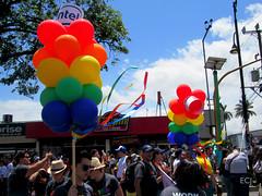 Globos multicolores/ Multi-colored balloons (vantcj1) Tags: personas multitud gente urbano globos multicolores edificio rótulo letrero árbol cielo nubes marcha manifestación desfile gay lgbti diversidad igualdad orgullo