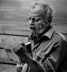 Reading Aloud. (Neil. Moralee) Tags: neilmoralee neilmoraleenikond7200 man read reader book reading publick people person mature wild hair face portrait old beard straggle scraggy skraggy rough neil moralee street perform performance poetry story tale entertain black white bw bandw blackandwhite nikon d7200 shirt