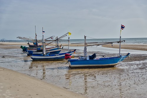 Fishing boats on the beach at low tide in Hua Hin, Thailand