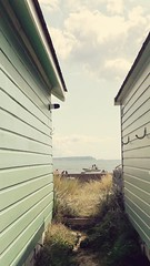 Needles between the huts.... (markwilkins64) Tags: markwilkins england beachgoers people boats theneedles isleofwight hengistburyhead dorset beachhuts grass boat sea solent summer beach sunny clouds uk seaside path pathway