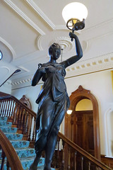 The Grand Hall (BarryFackler) Tags: iolanipalace palace hawaiianmonarchy royalresidence indoor nationalhistoriclandmark place building structure kingdomofhawaii honolulu nationalregisterofhistoricplaces 2018 mainstaircase thegrandhall koawood statue sculpture figurine artwork stairs staircase doorway lamp electriclight classical hawaii oahu hawaiianislands polynesia sandwichislands history architecture decor island culture heritage hawaiianculture hawaiianhistory monarchy royalty hawaiianheritage woman female wahine historical historic hawaiian barryfackler barronfackler