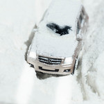 A terrain car is driving on a dirt road covered in snow thumbnail