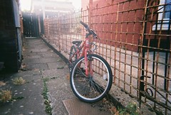 red bike (johnnytakespictures) Tags: disposable disposablecamera singleuse smile pocketsocket 35mm film analogue leamingtonspa leamington warwickshire bike bicycle cycle wheels transport vintage retro classic street chain chained lock locked red bmx mountain