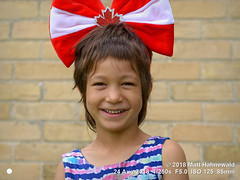 2016-06a Facing the Family 2018 (06) (Matt Hahnewald) Tags: matthahnewaldphotography facingtheworld people character head face eyes childreneyes mouth expression lookingcamera smile headgear headdress consent fun parentalconsent concept canada patriotism politicalcorrectness culture education childhood optimism diversity empowerment cultural brussels ontario ontarian canadian individual oneperson female child girl photo nikond610 nikkorafs85mmf18g 85mm 4x3 horizontal street portrait closeup headshot fullfaceview outdoor color posing iconic smiling pretty cheerful humour mapleleaf asiancanadian mixedrace visibleminority southeastasiancanadian clarity canadianflag redandwhite peoplekind