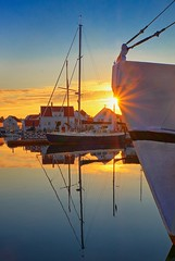 Evening sun, Norway (Vest der ute) Tags: xt20 norway rogaland karmøy sea water sunset sunstar boats sailboat reflections mirror evening serene sky bluesky clouds houses fav25 fav200