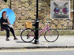 Umbrella, Bike and Poster (Padski1945) Tags: juxtaposition people peopleandposters lookoutbehindyou posters posterart postersandpeople poster streetart streetscene streetphotography