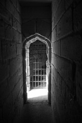 Free at last? (marktmcn) Tags: warkworth castle medieval building northumberland england light end tunnel corridor grille gothic arch stone wall blackandwhite monochrome d610