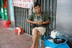 Seven Amulets (D. R. Hill Photography) Tags: bangkok thailand asia southeastasia city urban street streetphotography thai film analog analogue grain 135 35mmfilm contax contaxg2 g2 carlzeissplanar35mmf2 zeiss planar 35mm primelens fixedfocallength amulet buddhist kodak kodakfilm kodakportra400 portra portra400 man person portrait