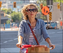 Lady Rider at Rideau & Sussex (Dan Dewan) Tags: 2018 dandewan bicycle street people person canon colour cyclist ottawa sunday summer woman august ontario canada glasses portrait canonefs18135mm3556is lady