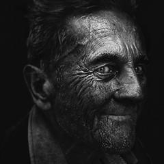 Man with sly smile (Ales Dusa) Tags: man portrait bw blackandwhite blackandwhiteportrait streetshot streetportrait face strongcontrast monochrome people outdoor human homeless slysmile blackbackground alesdusa canoneos5dmarkii ef50mmf18stm 50mm candidlight closeupportrait wrinkles oldwrinkledman elderly powerfulportrait humanity smile bestportraitsaoi