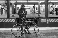 DANGER (John St John Photography) Tags: west4thstreet subwaystation mta newyorkcity newyork streetphotography candidphotography commuters youngwoman bicyclist bicycle peopleofnewyork bw blackandwhite blackwhite blackwhitephotos johnstjohnphotography