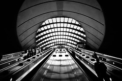 Canary Wharf (heinzkren) Tags: station tube metro ubahn architecture architektur urban geometry london schwarzweis blackandwhite bw sw monochrome exit rolltreppe stairs ausgang abgang light building gebäude city escalator subway underground indoor panasonic lumix gb ostrellina uk