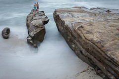Waves, Rocks and Kids in a Long Exposure (Photos By Clark) Tags: california cities subjects location beachshots canon2470 unitedstates northamerica sandiego canon5div locale places where us longexposure 6seconds waves rocks boys kids pacific water blue green tan sand swirl lightroom thesandiegoist