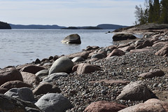 Shore with soft rounded granite stones in foreground (loj5407) Tags: red rock rough nature round textured strong stone shape solid natural mineral brown blue big form material heavy hard geology granite water sky horizon