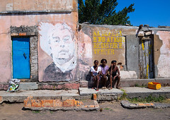 Angolan women sit in front of an old propaganda wall painting with Leonid Brejnev, Cunene Province, Cahama, Angola (Eric Lafforgue) Tags: adults africa angola angola180835 bilaiambundo buildingexterior cahama colourimage communism communist day developingcountries exterior facade groupofpeople horizontal leonidbrejnev mural outdoors politics politicsandgovernment portuguesecolony president propaganda representing soviet threepeople ussr wall wallpaintings womenonly cuneneprovince