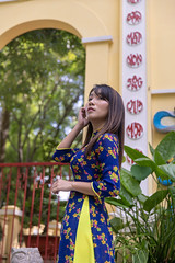 Young woman in Ao Dai standing in public park (Apricot Cafe) Tags: img105642 aodai asia asianandindianethnicities canonef2470mmf28liiusm hochiminhcity millennialgeneration vietnam vietnameseethnicity vietnameseculture carefree citylife colorimage cultures day forest happiness lifestyles longhair lookingaway lowangleview nature oneperson oneyoungwomanonly outdoors people photography portrait publicpark realpeople serenepeople smiling standing straighthair temple threequarterlength tourism tourist tradition traditionalclothing travel wall women youngadult hochiminh vn