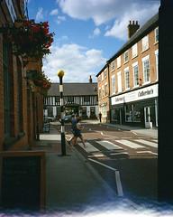 Southwell. (Esmik D'Aguiar) Tags: southwell nottinghamshire ga645zi fuji road crossing town pub shops blue clouds car wine red flowers uk lomography lomo
