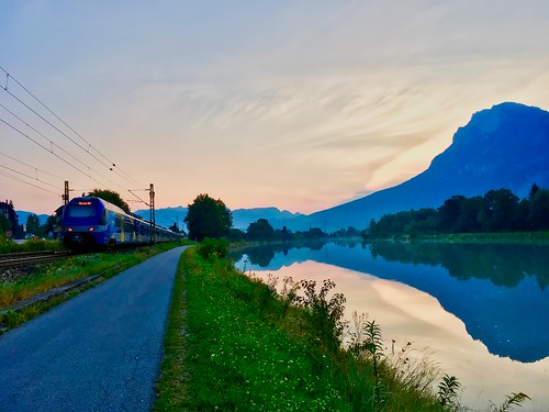 Early summer morning at the river Inn between Kiefersfelden and Kufstein with Kaiser mountains and Meridian regional train
