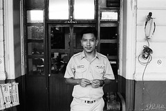 On Duty (D. R. Hill Photography) Tags: thailand thai bangkok asia southeastasia monochrome blackandwhite portrait man smile eyecontact railway station platform train trainstation official uniform contax contaxg2 g2 carlzeissplanar35mmf2 planar zeiss 35mm primelens fixedfocallength film analog analogue 135 35mmfilm kodak kodakfilm kodaktrix400 trix grain