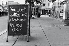 Past A Bookshop. Washington, D.C. (Sept. 2018) (Thomas Cluderay) Tags: washingtondc washington washingtonian dc district canon canon6d bookstore books streethumor blackandwhite blackandwhitephotography dupont kramers kramersbooks kramersbooksdc sidewalk sign chalkboard