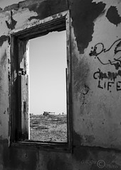 Room With A View (Dungeness)-03267 (G.K.Jnr.) Tags: landscape seascape building architecture foliage vegetation boat transport deserted discarded dilapidation sea seaside coastline beach shingle outdoor sky scenic interest touristattraction monochrome bw blackandwhite blackwhitephotos rural romneymarsh dungeness kent unitedkingdom fujix apsc xt2 graffiti historic