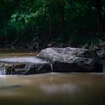 Little Waterfalls Flow Over Rocks on a Silty Creek thumbnail