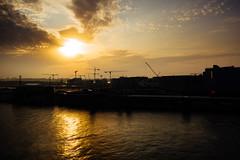the yellow haze of the sun (miemo) Tags: dji europe finland mavic2 mavic2pro aerial clouds constuction cranes drone evening helsinki jätkäsaari reflection sea silhouette sky summer sunset uusimaa fi