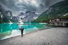 Wild world (Toukensmash) Tags: alps wild world alpine mountains mountain scene landscape austria italy trip vacation wide angle dark mood moody rain rainy storm lago braies lake pragser wildsee girl human element umbrella lady pentax k1 rokinon 14mm europe europa dolomites boat boathouse