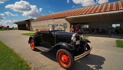 1930s Ford Model A Roadster - Guelph Airpark, Ontario (edk7) Tags: olympuspenliteepl5 slrmagic8mm14rectilinearultrawideanglemanualfocuslens edk7 2018 canada ontario guelph guelphairport cnc4 guelphairpark aerodrome tigerboysaeroplaneworksflyingmuseum annualairday2018 cloud sky 1930sfordmodelaroadster classic car twodoor convertible softtop vintage vehicle passenger automobile auto rust corrugatedgalvanizedsteelroof glider sailplane pavement grass person people male driver wirewheel hangar