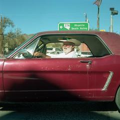 (patrickjoust) Tags: mamiya c330 s sekor 55mm f45 kodak portra 160 tlr twin lens reflex 120 6x6 medium format film c41 color negative manual focus analog mechanical patrick joust patrickjoust west united states north america estados unidos man driver driving red car beatty day nevada nv road sign portrait