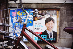 Bicycle with smiling politician (Eric Flexyourhead) Tags: nakazakicho 中崎町 kitaku 北区 osaka osakashi 大阪市 kansai 関西地方 japan 日本 city urban detail fragment japanese bike bicycle charinko チャリンコ jitensha 自転車 politician ad advertisement poster sonyalphaa7 zeisssonnartfe35mmf28za zeiss 35mmf28