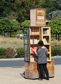 Woman visiting a free library in front of the Gare du Fontainebleau-Avon, France