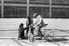 020571 20 (ndpa / s. lundeen, archivist) Tags: nick dewolf nickdewolf blackwhite blackandwhite 35mm film bw february 1971 1970s boston massachusetts cambridge lechmere lechmeresales firststreet parkinglot photographbynickdewolf man bike bicycle building windows chold boy kneel kneeling water meltingsnow alexander woman maggie hat facialhair sideburns mustache moustache