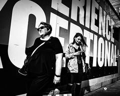Ex-ceptional (Kieron Ellis) Tags: people woman women phone sunglasses headphones jacket bag wall candid street contrast light shadow letters blackandwhite blackwhite monochrome