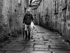 Man in the alley (alexhesse.de) Tags: porto regen man alley portugal bnw monochrome olympusomd cobblestones noiretblanc streetphotography streetfotografie street streetwalk noireetblanc schwarzweis schwarzweiss rain umbrella