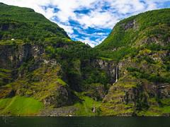 Waterfalls in the Aurlandsfjord (RobertCross1 (off and on)) Tags: 1250mmf3563mzuiko aurland aurlandsfjord em5 europe hordaland norge northsea norway omd olympus bluesky cliffs clouds fjord landscape ocean trees water waterfall