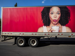 RED (MomoFotografi) Tags: truck red van fun advertising black blackgirl girl funny contrast colorful blue bluesky street streetphotography olympus 12mm zuiko cool milk milkshake camion rouge bleu cloud clouds sky vans tire tires vibrant summer montreal city road